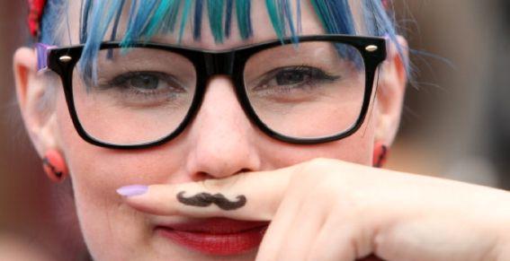 Moda hipster. Una chica moderna luciendo su bigote